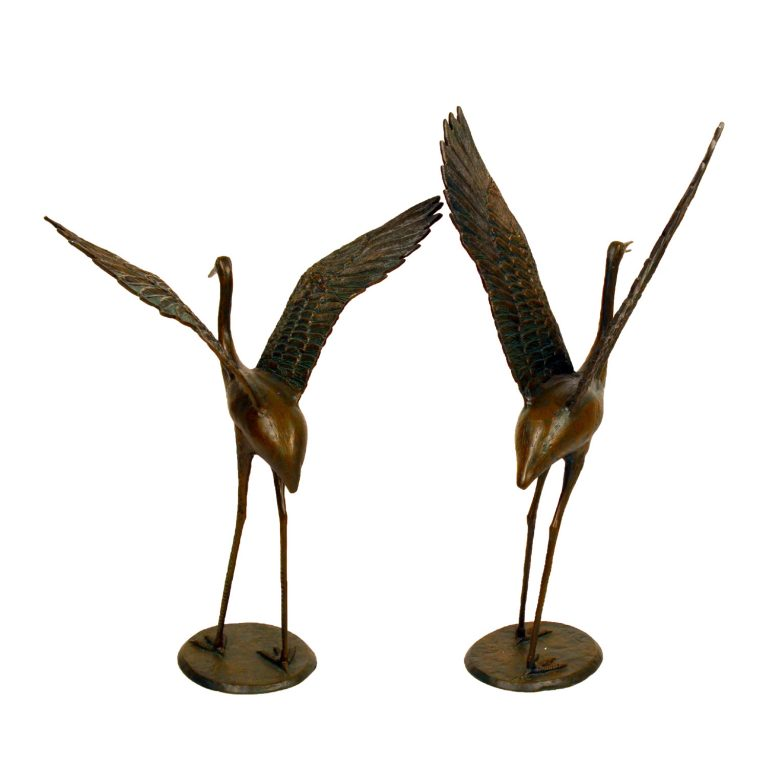 bronze cranes outstretched wings face on